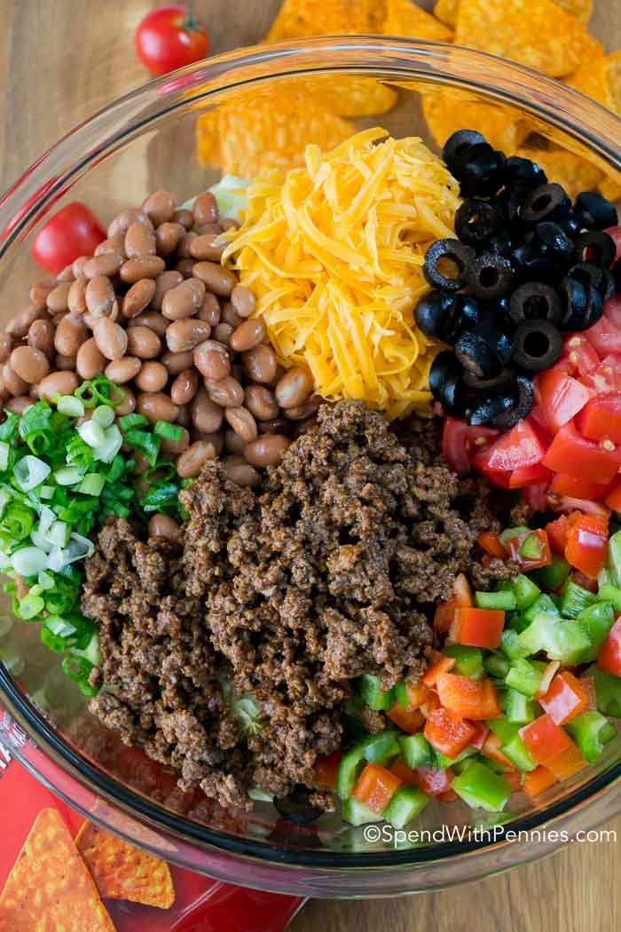 I have been asked for this taco salad recipe countless times! Dorito Taco Salad has loads of seasoned ground beef, veggies, beans and Doritos in a zesty sauce! #tacosalad