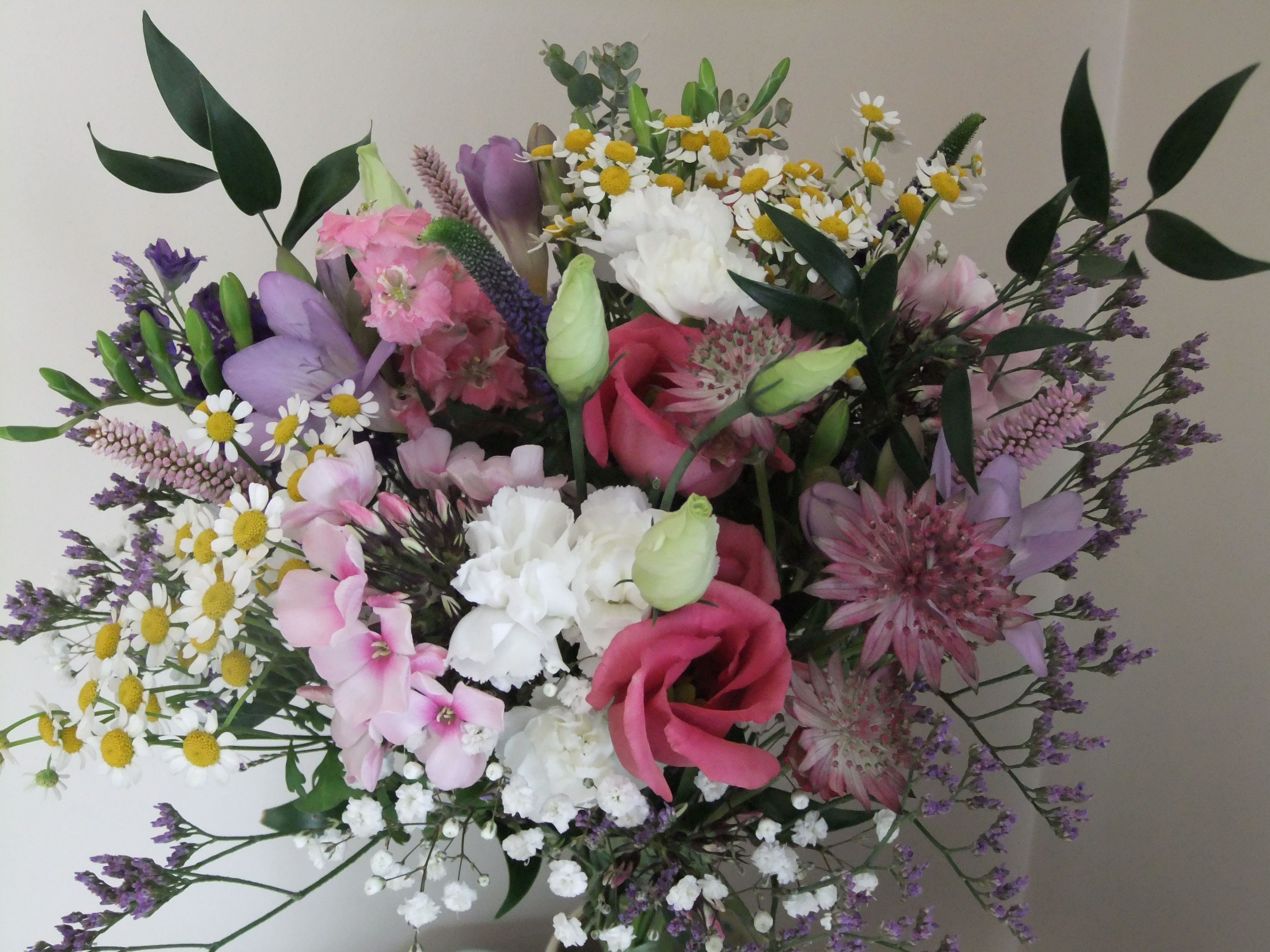 A pretty bridal bouquet of country garden flowers in pastel colours ...