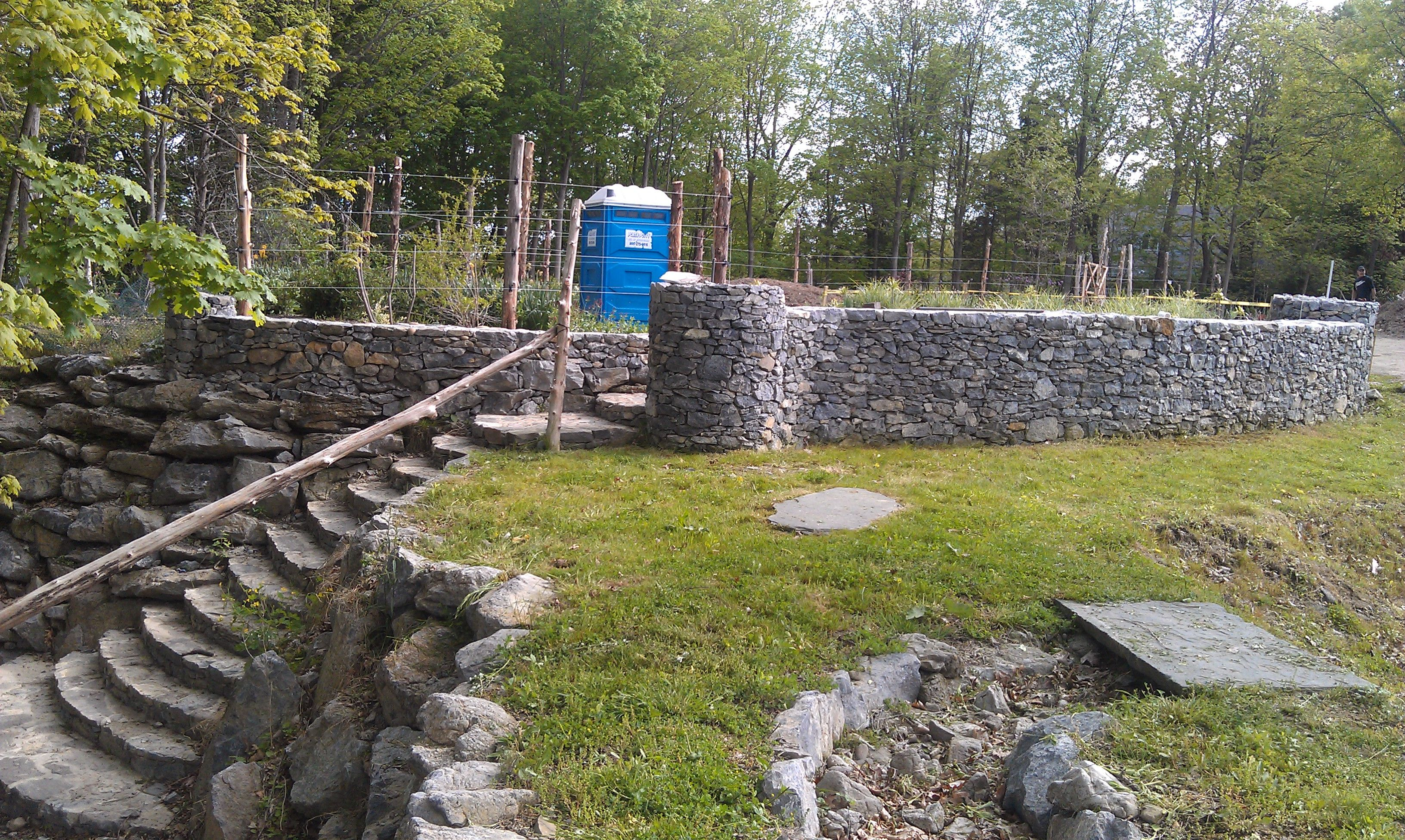 Curving stone stair case, curving stone walls, dry stream bed with natural blue stone slab bridge, ending in waterfall into what will be a large pond,