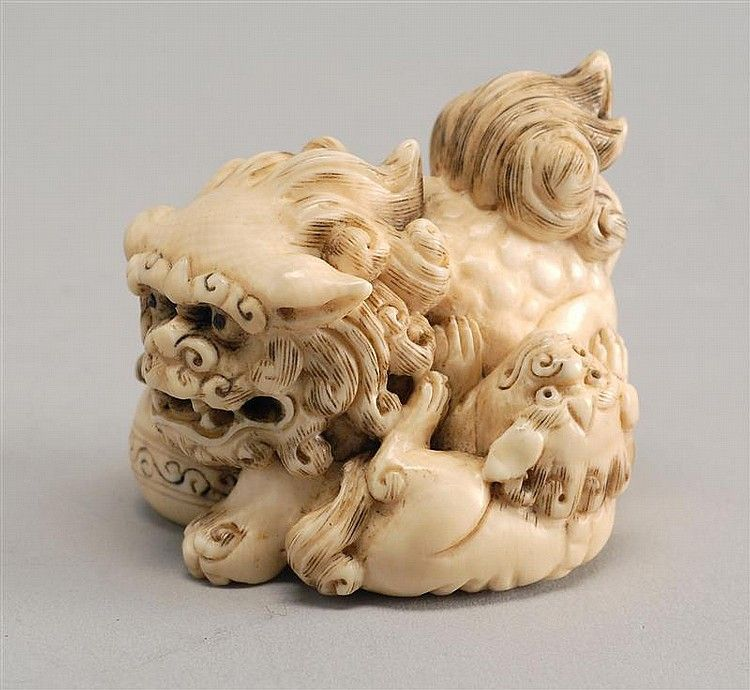 Asiatische Lions ivory netsuke depicting two lions with a brocade signed
