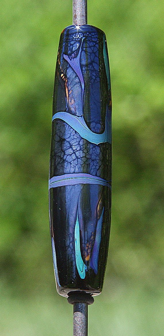 A barrel-shaped bead in a base of metallic black. This bead has striking glass in blue and aqua, and apricot for a wonderful contrast. The dimensions are: 44.4mm (1.75) long, 10.3mm (.40) wide, with a 2.5mm hole.