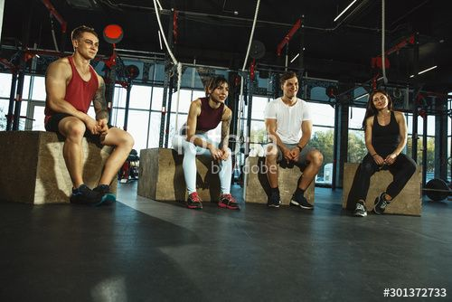 A group of muscular athletes doing workout at the gym. Gymnastics, training, fitness workout flexibi...