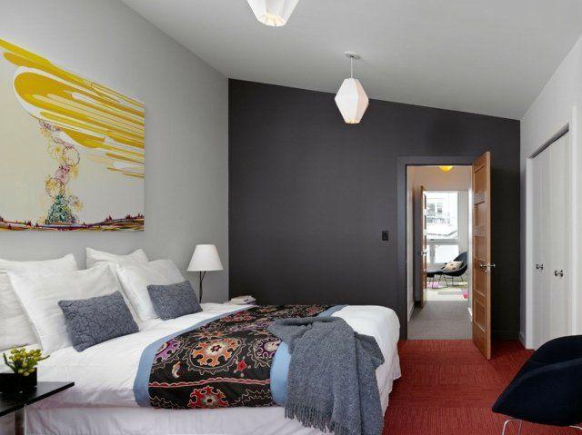 chambre grise avec un tableau mural et grand lits décoré de coussins