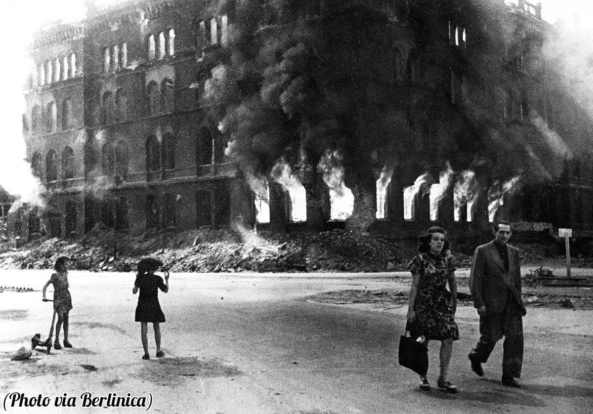 A couple walking down Dircksenstrasse and the burning streets of Berlin in the final days of the war, 1945.