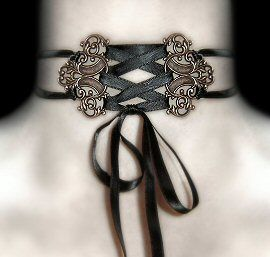 Ashes to Ashes Corset Choker    Two intricate Victorian style antique gold tone filigrees create a wonderful corset effect choker.  Tied with cascading black satin criss cross bow. Fastens at the back with two more black satin bows