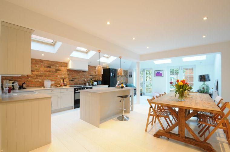 ampia e moderna cucina con isola e tavolo da pranzo con vaso e fiori ...
