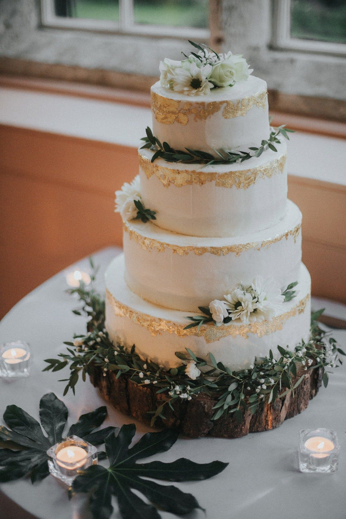 Four tier iced cake decorated with gold leaf and fresh flowers