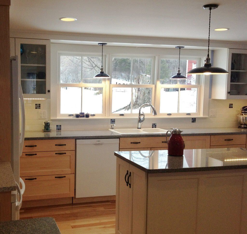 Light shaker cabinets with grey countertops and dark accents.