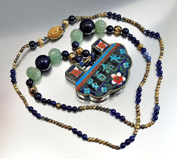 An amulet lock pendant for wishing someone longevity, good luck and protection! The wide lock pendant is reversible with one side having a white flower design on a cobalt background with turquoise accents and the reverso turquoise letters with the meaning of wishing someone longevity. The pendant is suspended from a hand knotted strand of melon shaped jade beads and genuine lapis beads alternating with faceted gold brass beads. The necklace ends with a filigree clasp hallmarked China.