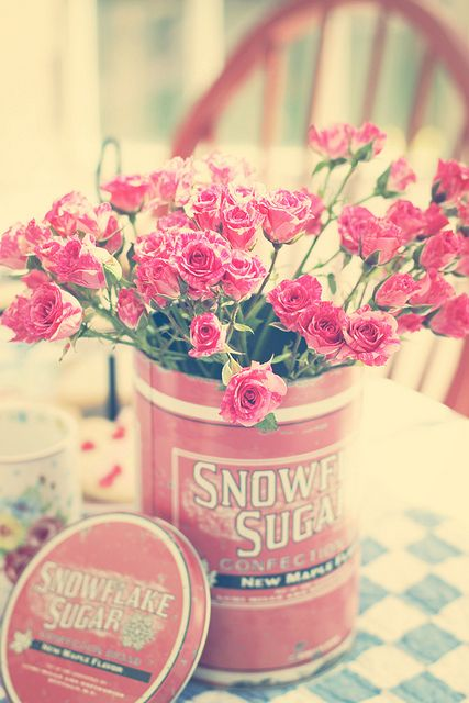 Put a glass or plastic receptacle in a tin and use it as a vase / Looks great on the kitchen table