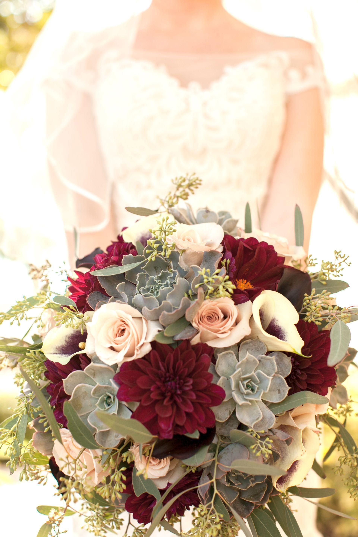 Burgundy dahlia, succulents, white calla lilies, roses