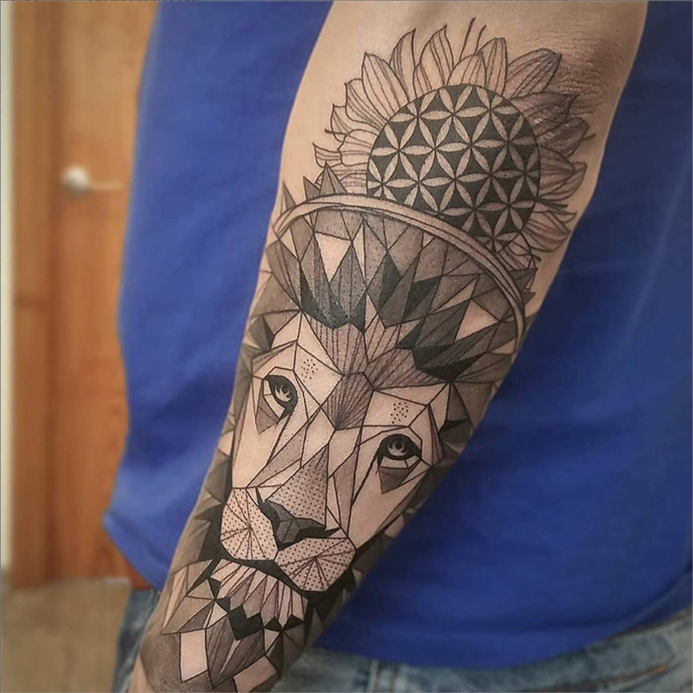 Freshly done black and gray graphic lion on mans arm artist janis