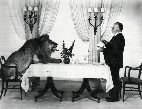 Alfred Hitchcock serving tea to Leo the Lion, the mascot for MGM Studios