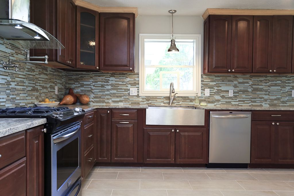 Cherry Cabinets With Mosaic Glass And Stone Backsplash