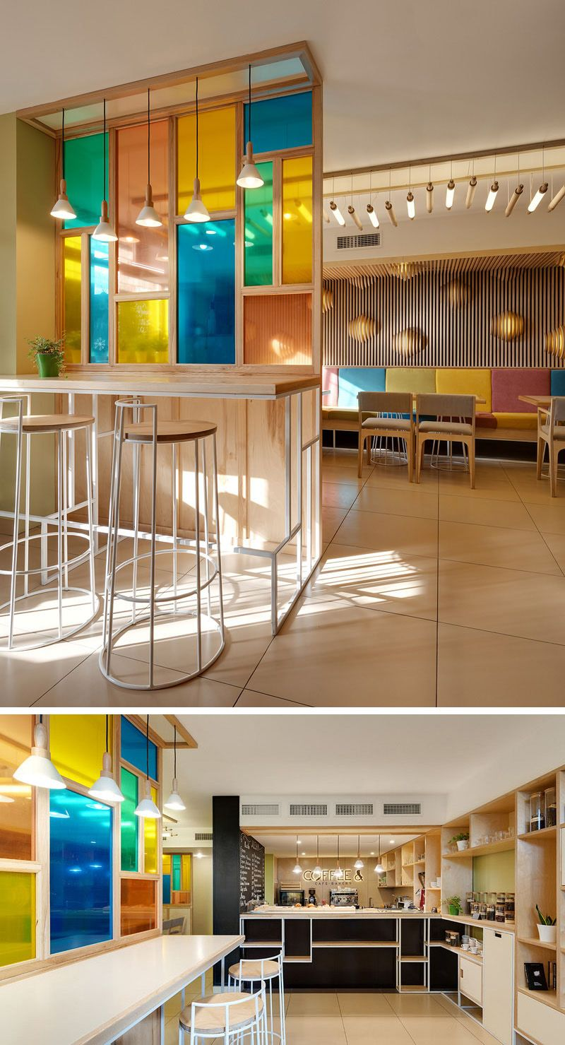 The colored glass paneled wall in this cafe bakery creates a unique feature that matches the rest of the decor