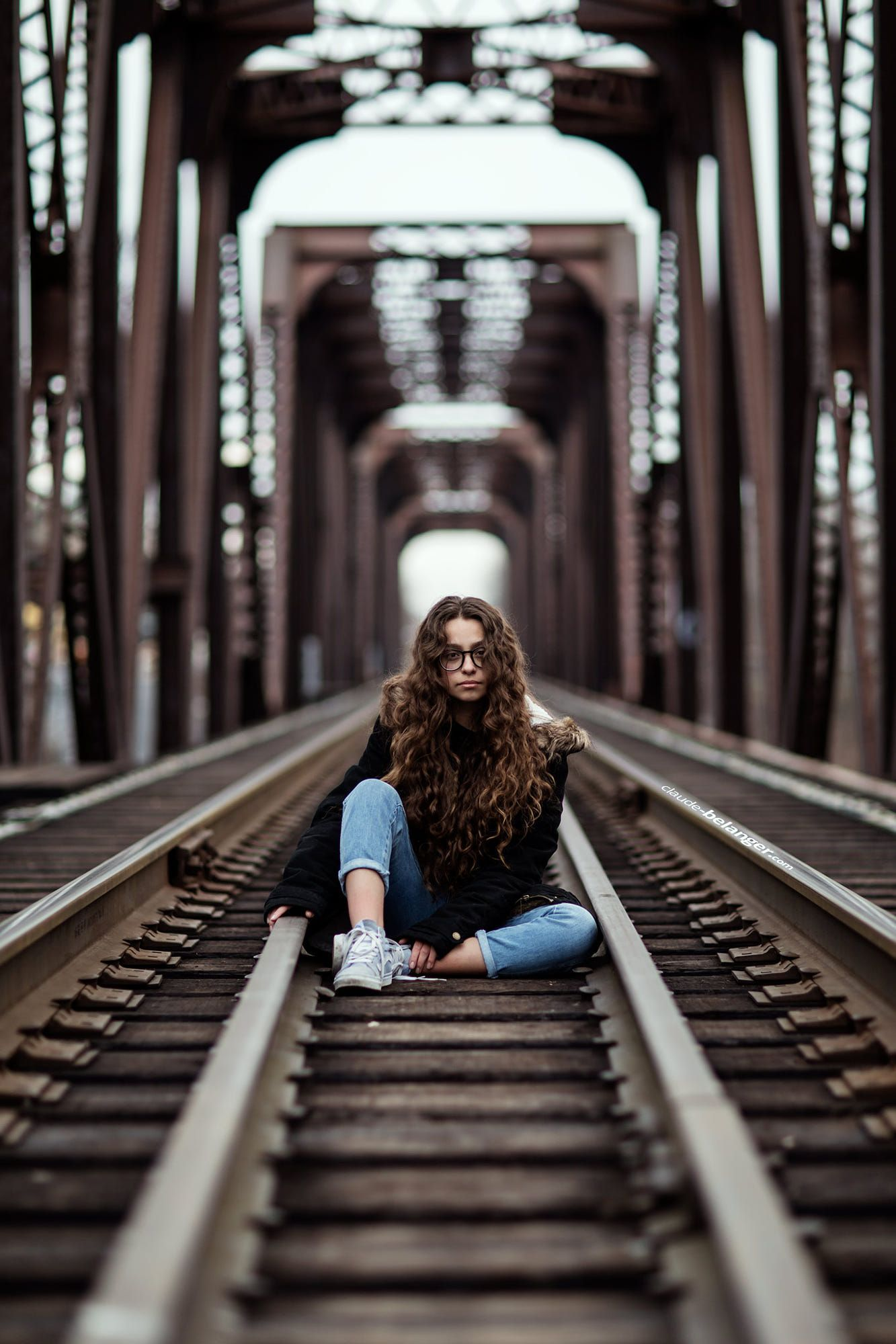 young girl sitting on an abandon train track under a bridge