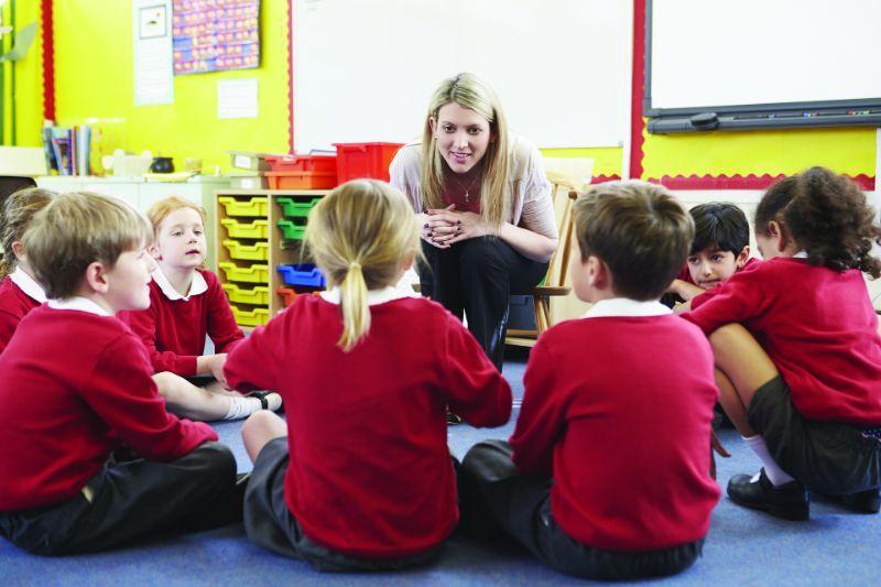 Lehrer sitzt im Kreis mit Kindern