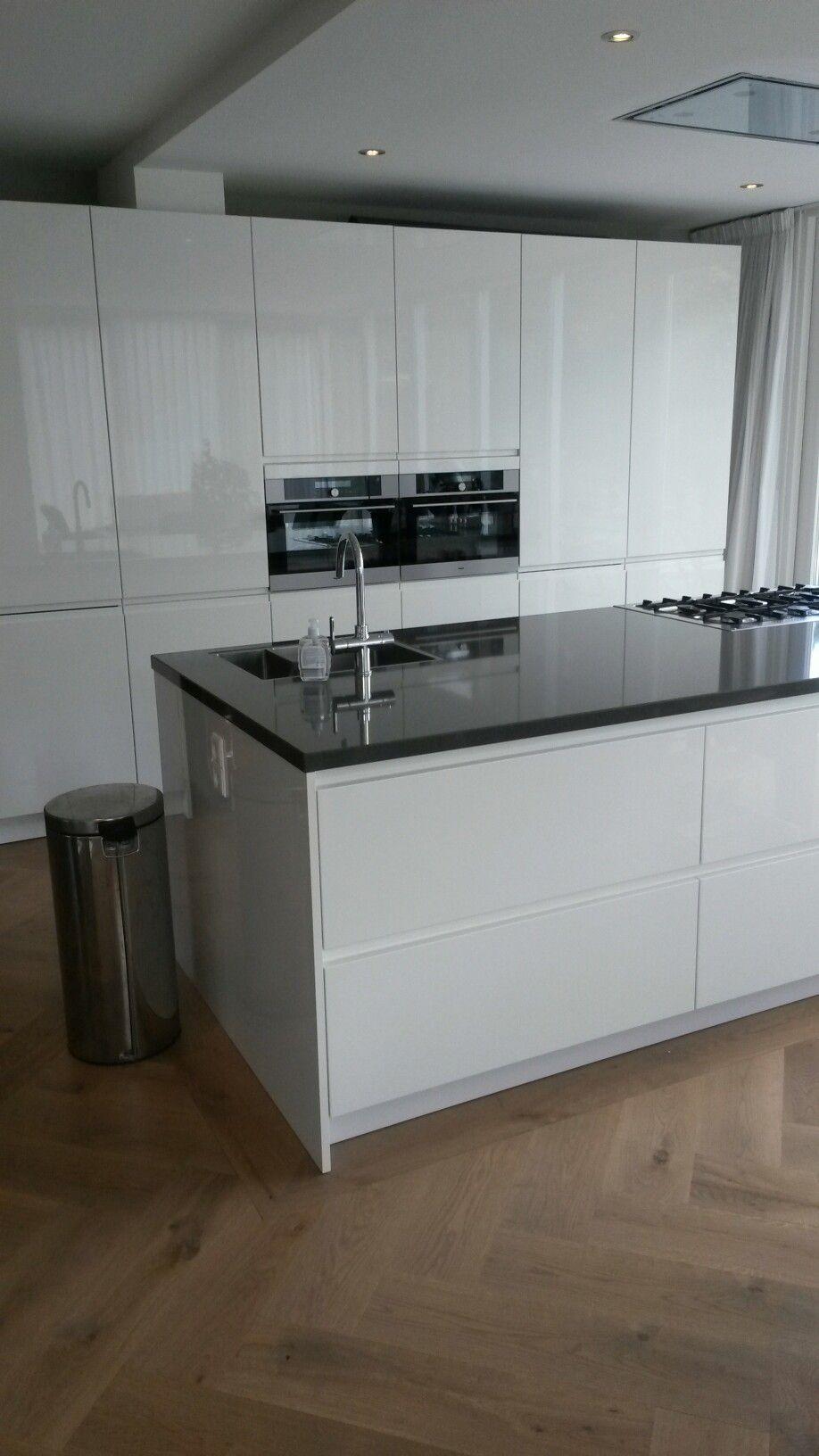 Hoogglans keuken met groot kookeiland en zicht op de tuin for Keuken op houten vloer