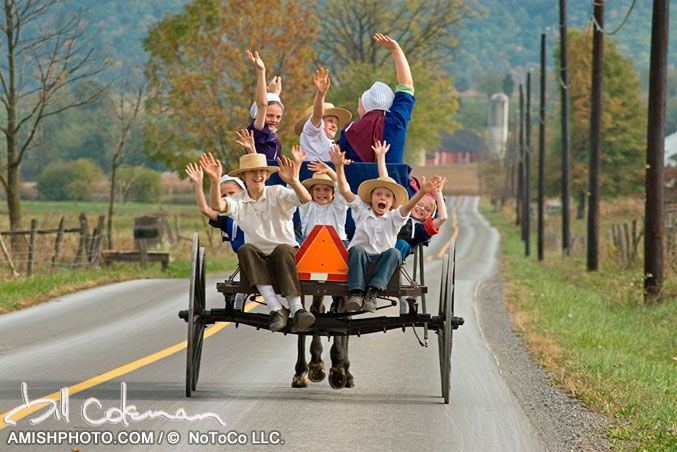Schools out a group of amish children smile and wave from the back of a wagon at the end of a school day