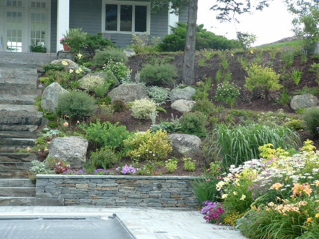 Slope landscaping with stone residence pool side for Low maintenance sloping garden ideas