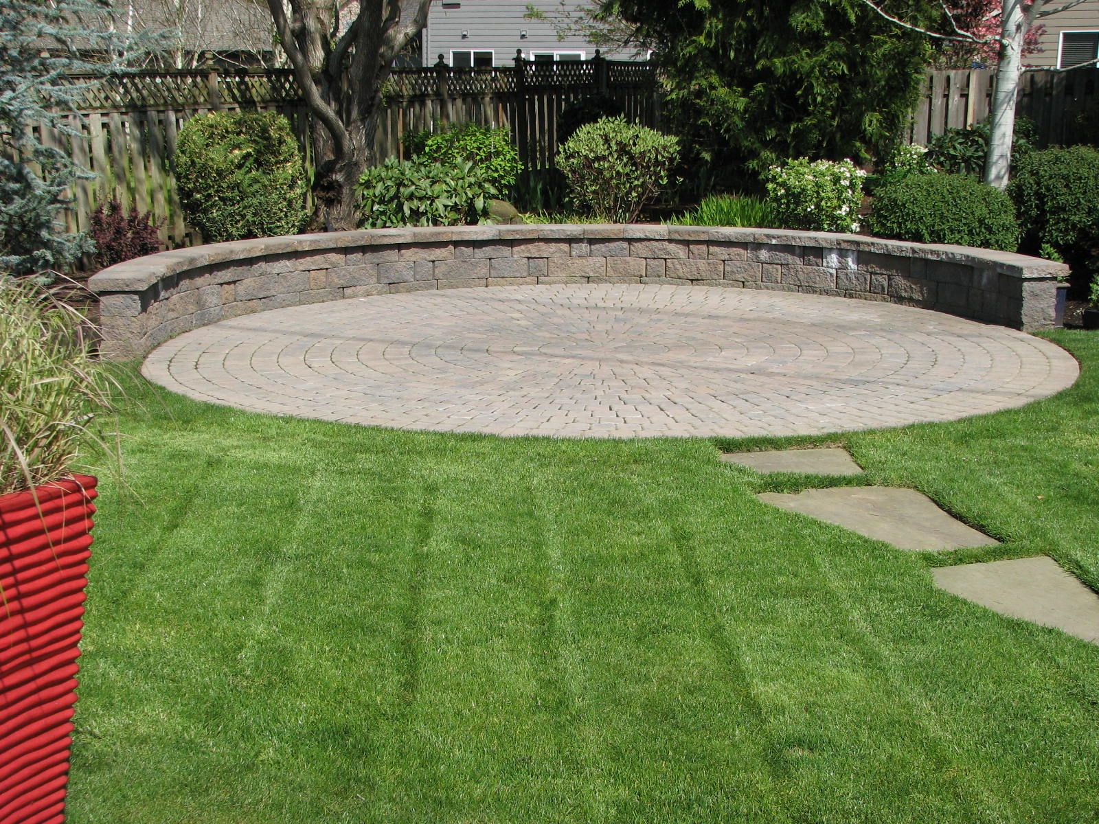 A circular paver patio and seating wall create a ...