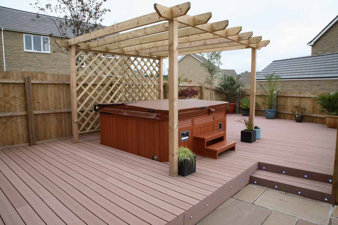 redwood vertigrain deck surrounding a hot tub with a pergola over it   decking  timbertech
