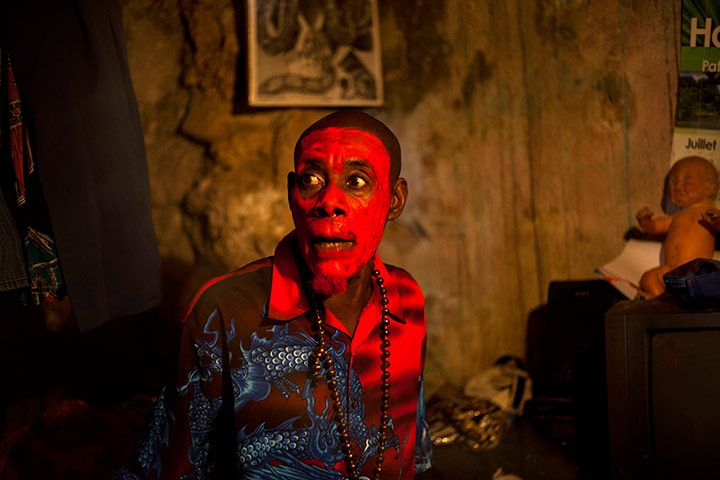 Dieu Nalio Cherry took a remarkable set of photographs of snake handler Saintilus Resilus during pre-Lenten Carnival celebrations in Petionville, Haiti. Here, he talks to his assistants as they get ready to perform  Photograph: Dieu Nalio Chery/AP