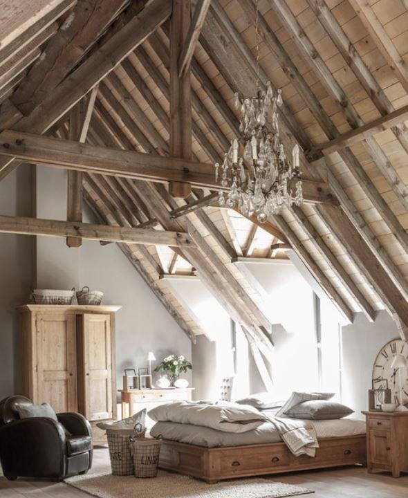 Poutres apparentes , armoire en chêne naturel, fauteuil club en cuir et lustre en cristal donne un style cosy à cette chambre.