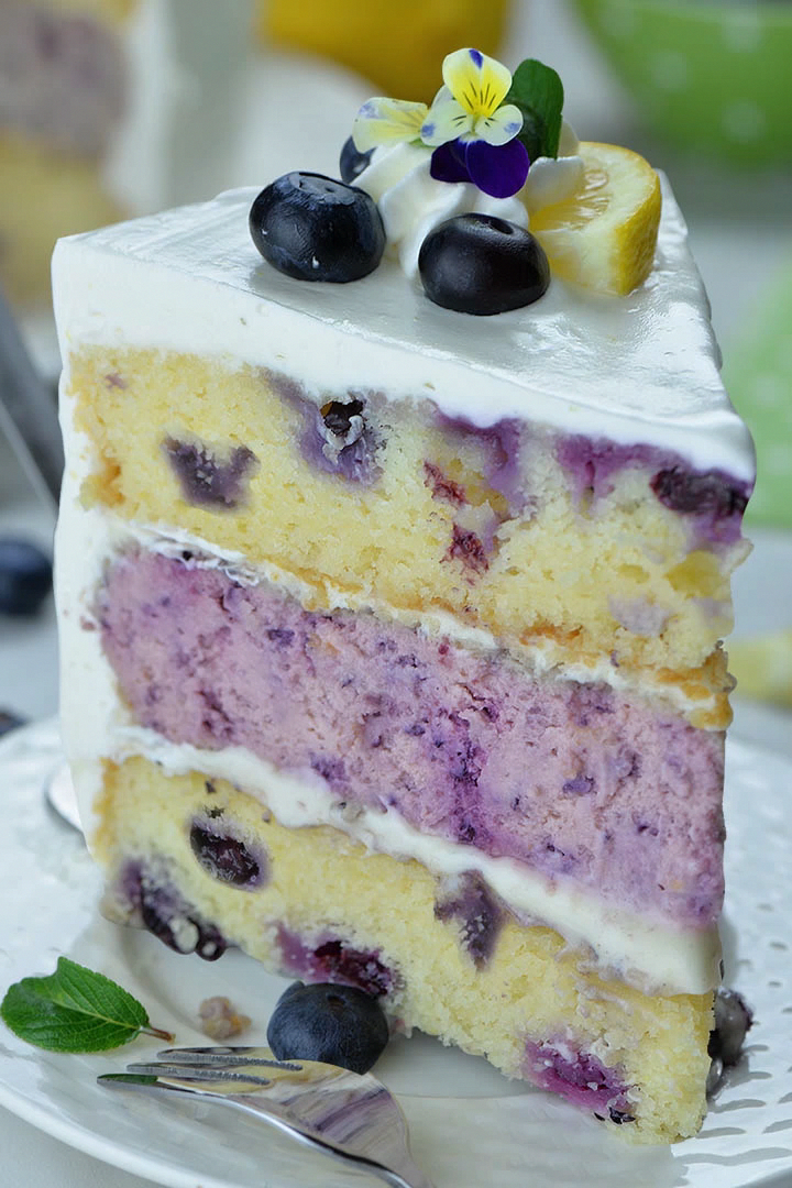 A decadent blueberry cheesecake kissed by lemon hiding inside a layer cake. Perfect summer cake.