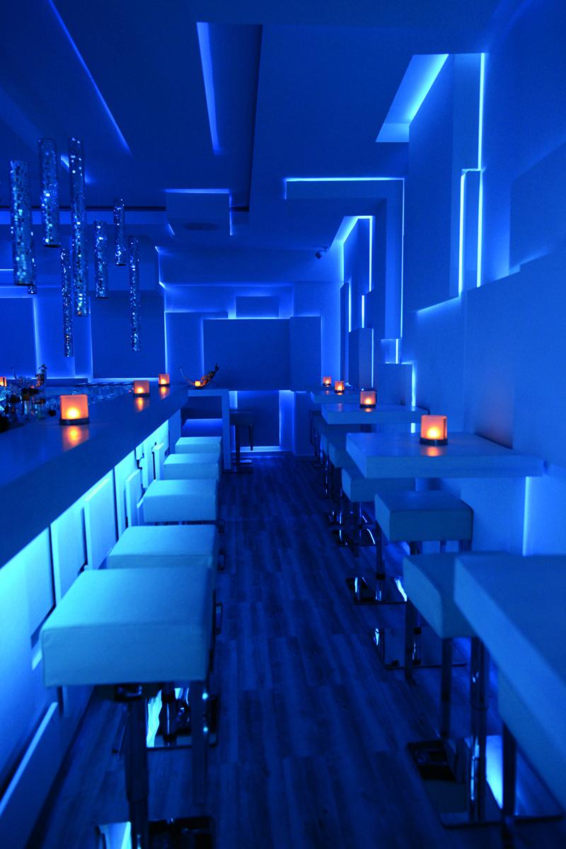 un locale dall'atmosfera cool e moderna creata grazie all'illuminazione con strisce led blu ...