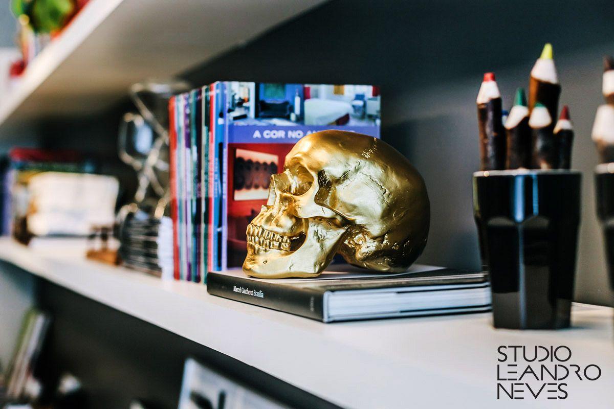 Caveira dourada na decoração da estante no Studio Leandro Neves.