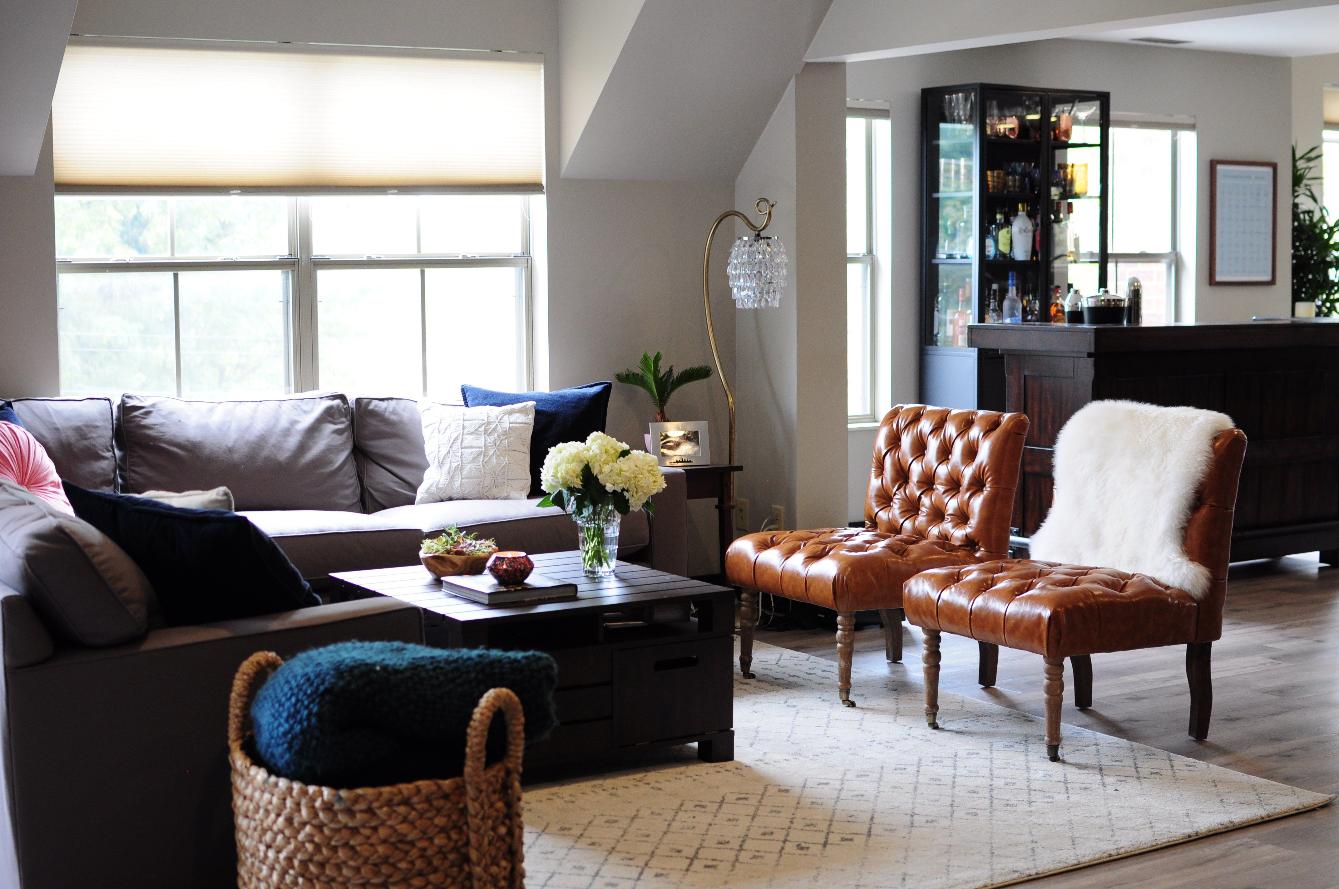 Eclectic Glam Condo Reveal The Living Room is part of Eclectic Living Room Glam - Today I'm excited to share the next room in the Eclectic Glam Condo Reveal The Living Room! If you missed the dining room and entertaining area reveal, this is the beautiful open floor plan condo of Client L and her boyfriend  They just moved in together and have different styles, hers being eclectic (rustic, industrial, and glam), and his being masculine  We worked together to blend their styles and create a space that finally felt like their home together  Here's a look at the living room! BEFORE EDESIGN They wanted a space with a lot of seating for entertaining, so we went with a modern sectional sofa and pair of tufted leather accent chairs  They both work from home, so this walnut coffee table provides plenty of storage for extra cords, notebooks, folders, etc  We added a touch of feminine glam with a blush round velvet pillow and sheepskin rug, as well as eclectic interest with macrame pillows and a Moroccan trellis rug  AFTER Winter is coming! Extra throws are stored away perfectly in this beachcomber basket, a personal favorite of mine! Last but not least, we'll be sharing the home office soon  Hope you'll check it out! GET THE LOOK xx, Related