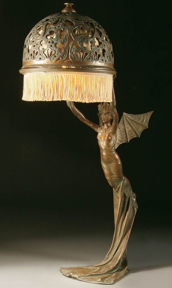 AN ART NOUVEAU BRONZED METAL FIGURAL TABLE LAMP Probably Austrian Circa  1900 Of A Winged Nymph, After A Model By R. Elias. With Pierced Scrolling  Filigree ...