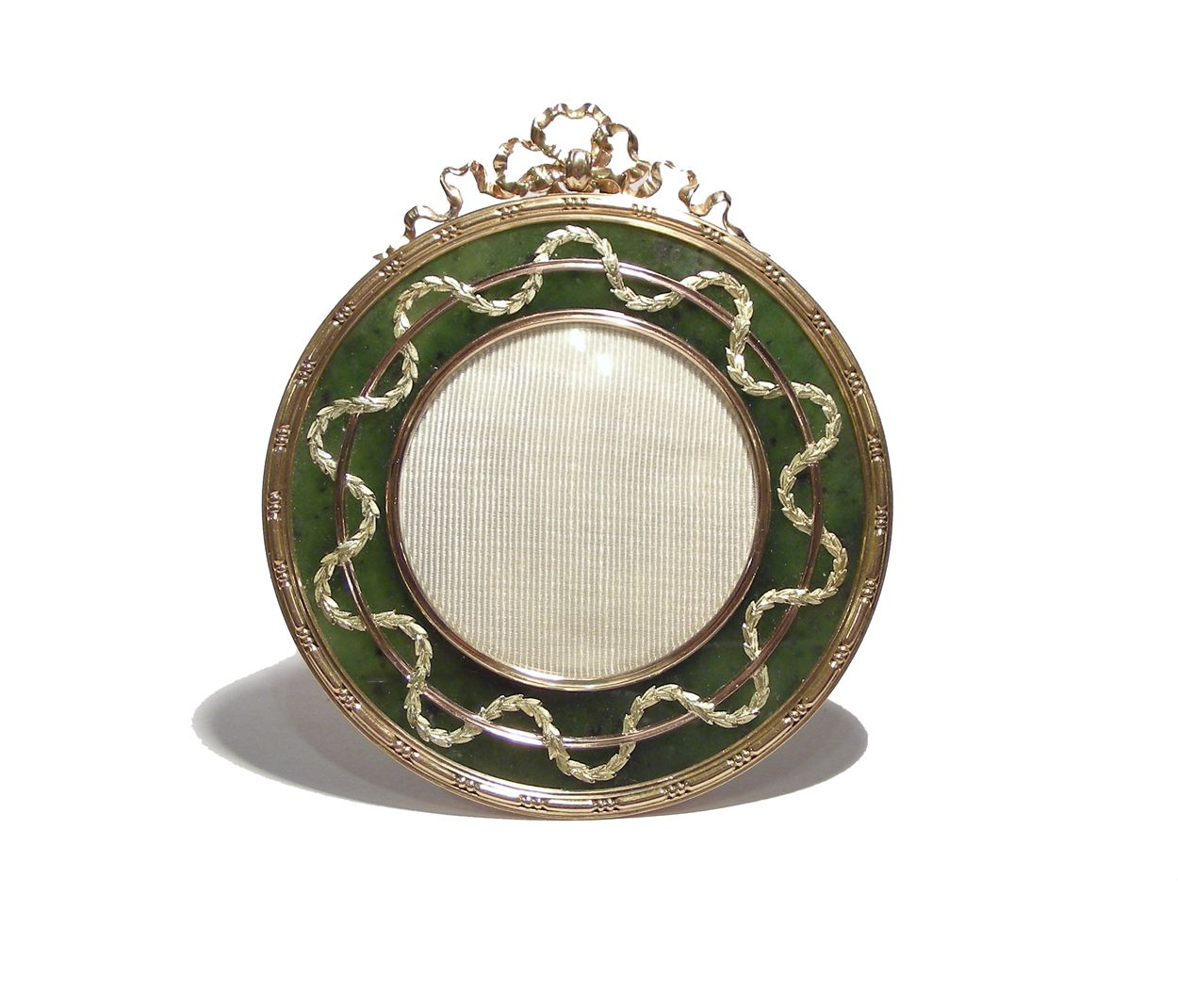 A two coloured gold nephrite frame by Fabergé, workmaster Michael Perchin, pre-1896, formed from a circular panel of nephrite, centred by a circular aperture beneath glass held in a reeded gold bezel, the opening encircled by undulating trail of finely chased and richly coloured gold laurels, bordered in red gold with a three-dot and dash motif and surmounted by a tied red gold bow, supported on a scrolled gold strut and backed with ivory.