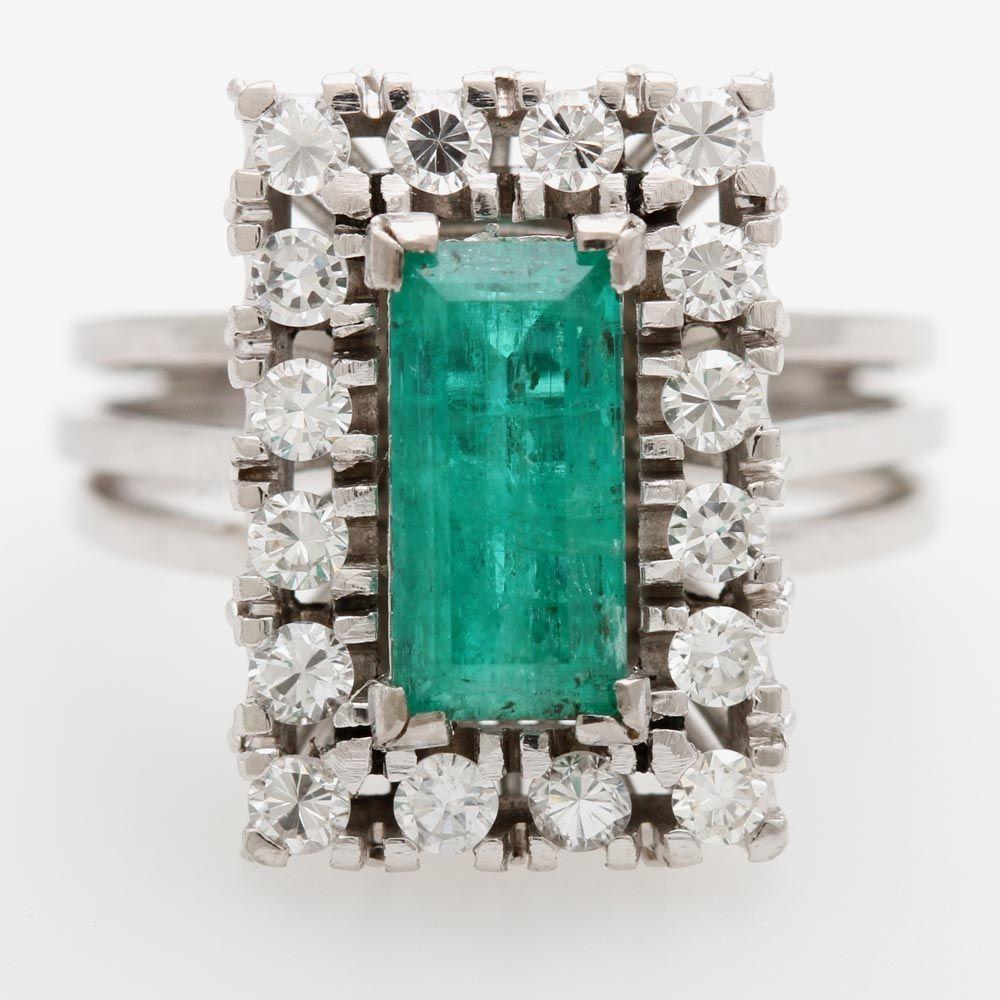 Damenring m. einem rechteckigen Smaragd (Einschlüsse), entouriert von Diam.-Brillanten zus. ca. 0,5
