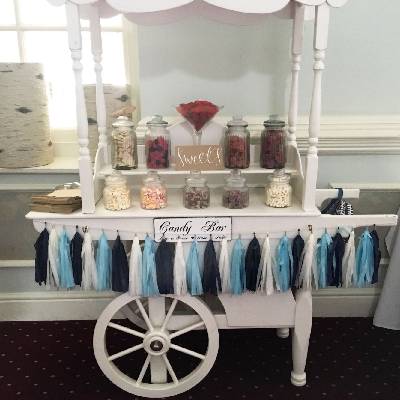 Candy cart with blue and white tassel garland christenings