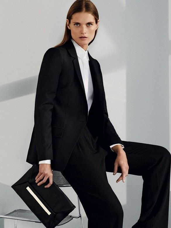 Malgosia Bela wears a white collared shirt, black blazer, trousers, and a black envelope clutch | @andwhatelse