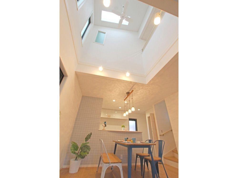 吹き抜けのあるリビング 空間に開放感をもたらす吹き抜けは ダイニングスペース上部に トップライトから差し込む陽光が室内を明るく照らします 対面式の キッチンと吹き抜けで おしゃれなカフェのようなイメージです 吹き抜け 天窓 トップライト 高い天井 対面