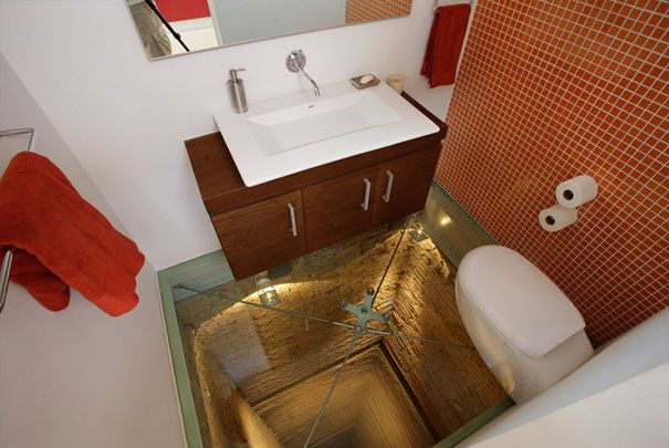 Bathroom with glass floor over 15 story elevator shaft. This is really cool.... but, how do you replace the lightbulbs that shine down the shaft?
