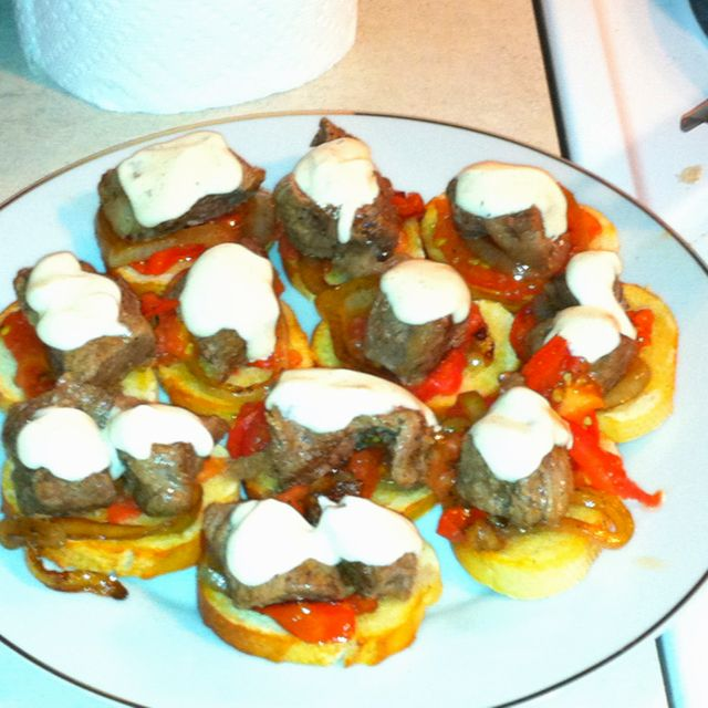 Beef tips with sautéed red peppers on toasted French bread with mayonnaise sauce topping.