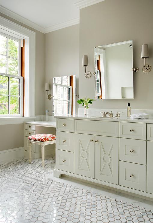 Ivory and beige bathroom features a frameless rectangular pivot ...