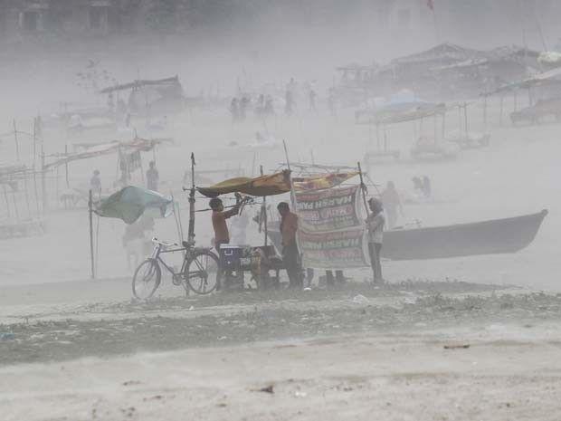 Homem segura lona de sua tenda armada em uma margem do rio Ganges durante tempestade de areia nesta segunda-feira (13) em Allahabad, na Índia (Foto: REUTERS/Jitendra Prakash)