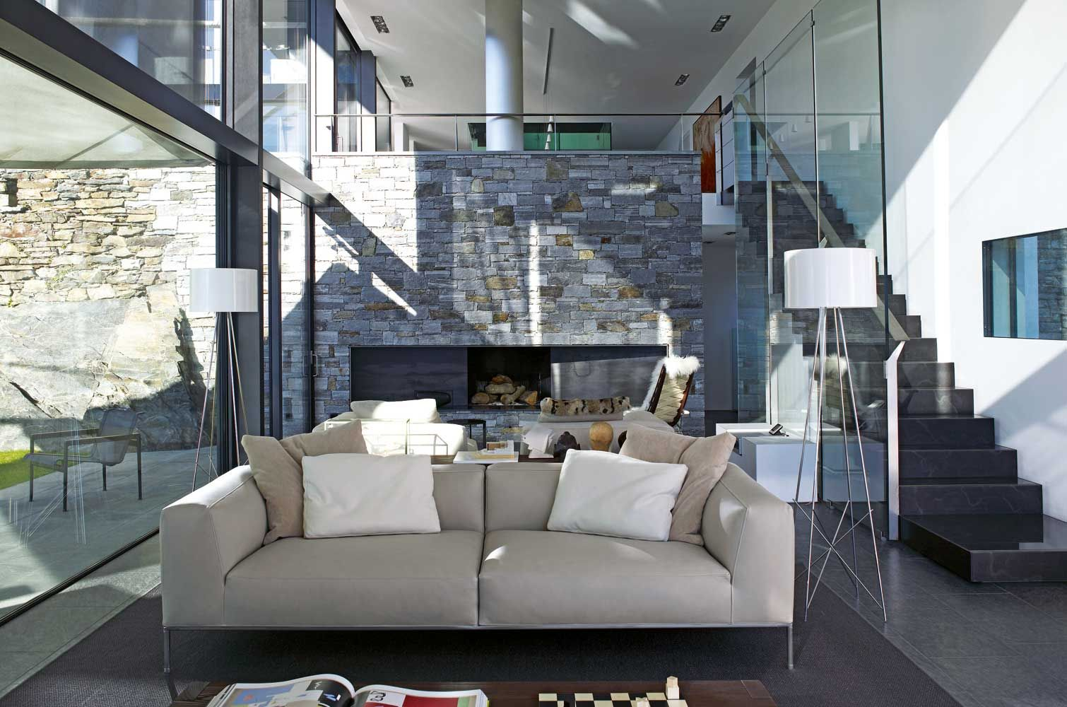 Modern living room with fireplace staircase and glass divider