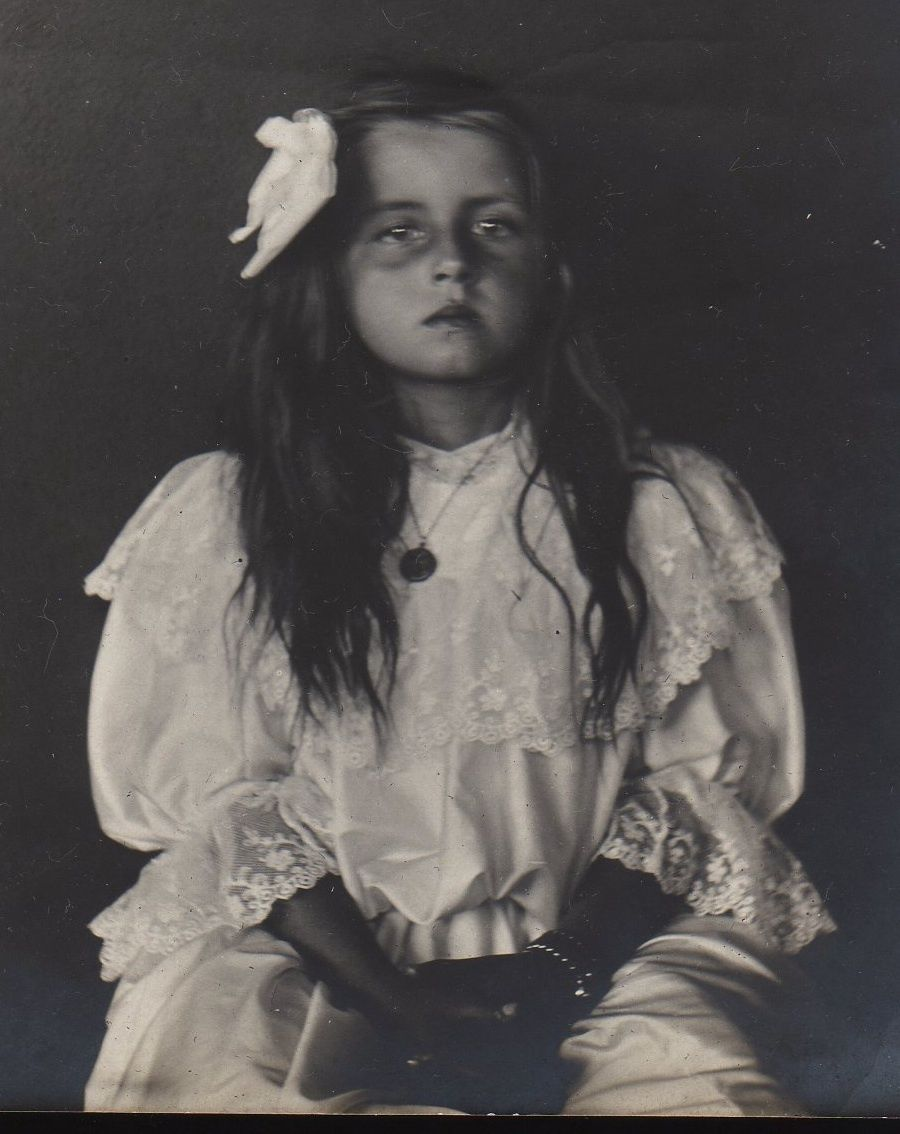 Apparently she was quite dead when her parents had this memorial photograph taken of their deceased daughter. The eyes were often 'painted' in later by the studio.