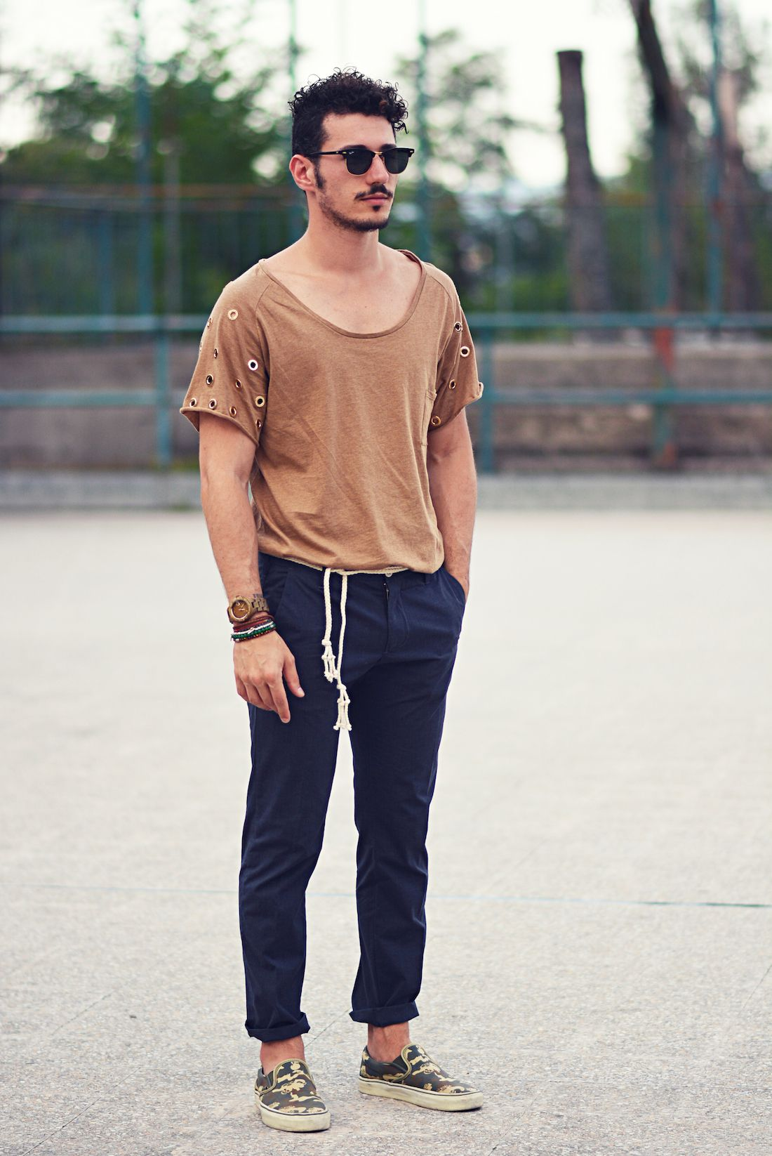 Shop this look for $59: http://lookastic.com/men/looks/tan-crew-neck-t-shirt-and-navy-chinos-and-dark-green-slip-on-sneakers-and-black-sunglasses/3598 — Tan Crew-neck T-shirt — Navy Chinos — Dark Green Camouflage Canvas Slip-on Sneakers — Black Sunglasses