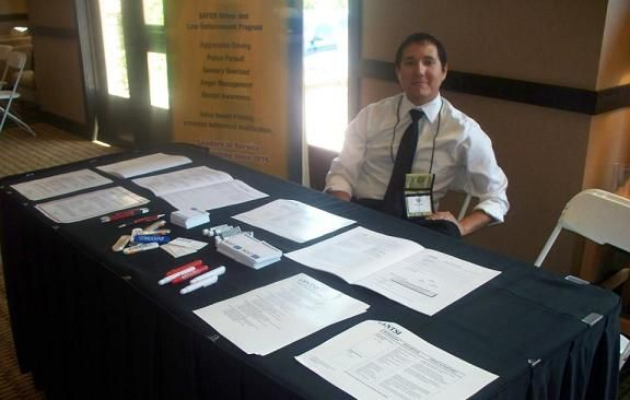 At the ACA Conference in Prescott, Arizona, NTSI's Alex Smith shows how neatly organized one's exhibit table can be before the rush of conference attendees. The Arizona Courts Association holds regular conferences for the benefit of court personnel. NTSI supports their efforts and proudly participates in the conferences.