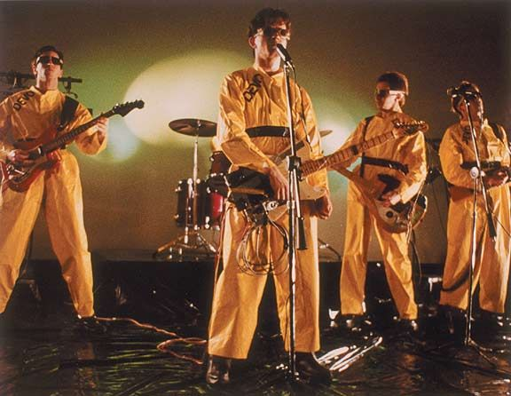 Members of Devo, a rock band of the 70s wearing yellow suits- similar to those from Revenge of the Nerds (1984)
