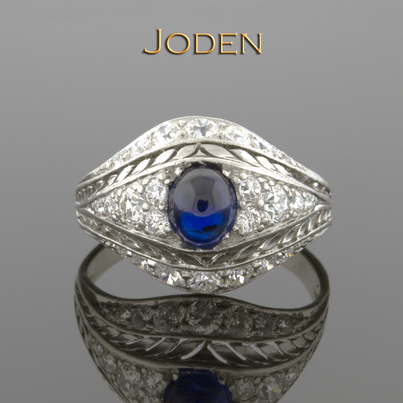This ring is unique in so many ways with open details in a wheat pattern, bright diamonds and a beautiful blue cabochon sapphire. The center holds one high cabochon sapphire that measures approximately 6.0 x 4.5 millimeters with a weight of approximately 1.00 carat. Accenting the design are 24 old European cut diamonds that have a weight of approximately .55 carat total weight. These diamonds have an average color grade of G-H and an average clarity grade of VS(1-2).