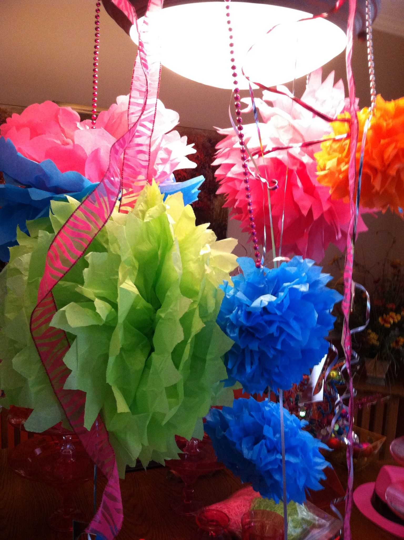 We made these puffs with tissue paper and hung with ribbon and beads.