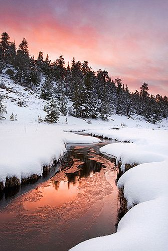 The morning after nearly a foot of spring snow fell in Rocky Mountain National Park near Estes Park, Colorado. A nearly frozen over stream made for a perfect spot to reflect dramatic sunrise color.